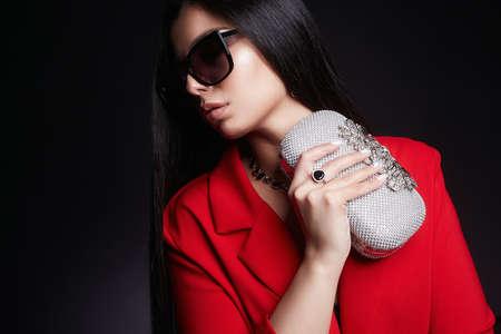 portrait de mode de belle femme avec pochette et lunettes de soleil.jewelry. jolie fille
