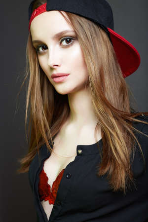 Fashionable beautiful Girl in red Cap and bra. Teenager style pretty young woman. Healthy Hair