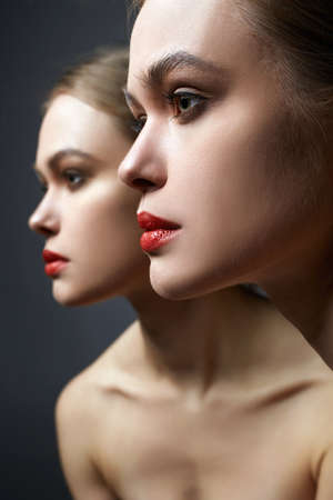 Beautiful Girl looking in the mirror. Young woman with red lips make-up Banco de Imagens