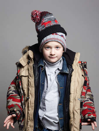 Funny boy in two hats and winter outerwear. fashion kid. child. teenager wore all his clothes