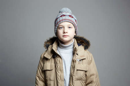 Fashionable Boy in winter outerwear. fashion kid. child. stylish teenager in knitted hat Banco de Imagens