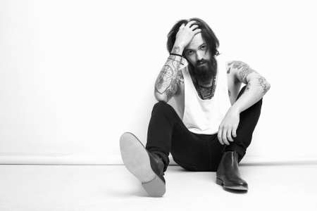 monochrome fashion portrait of handsome man in shoes.Brutal bearded boy with tattoo