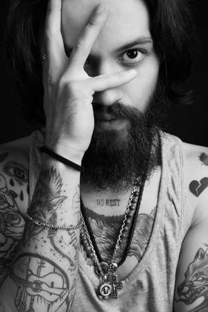 black and white portrait of handsome man with beard and tattoo. bearded hipster boy