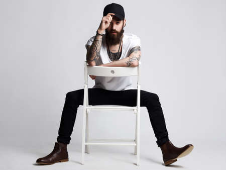 Tattooed handsome Man in Hat sitting on a chair. Stylish hipster boy with tattoo
