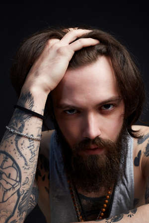 drunk man with beard and tattoo. bearded hipster boy portrait