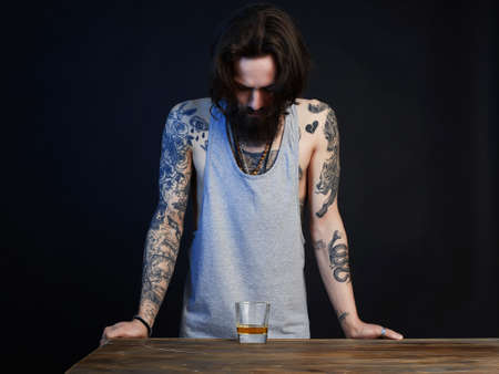 drunk man with beard and tattoo. man with glass of whiskey bearded hipster boy portrait