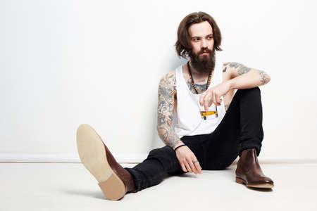 drunk man with beard and tattoo. sitting on the floor man with glass of whiskey. bearded hipster boy portrait