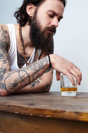 man with beard and tattoo. man with glass of whiskey. bearded hipster boy in Bar Banco de Imagens