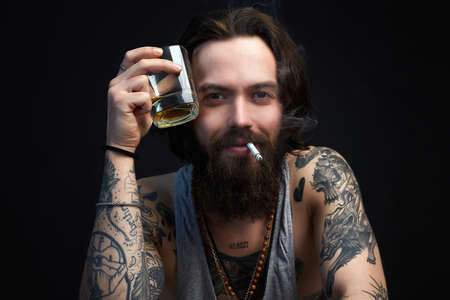 smiling man with glass of whiskey and cigarette. smoking hipster boy with beard and tattoo. Banco de Imagens