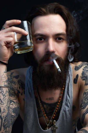 man with glass of whiskey and cigarette. smoking hipster boy with beard and tattoo. Banco de Imagens