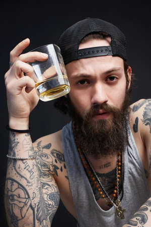 stylish handsome bearded man with tattoo enjoying whiskey. tattooed man in hat drinking a whiskey