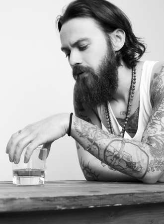 drunk man with beard and tattoo. man with glass of whiskey. bearded hipster boy portrait Banco de Imagens