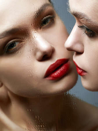 Beautiful Girl looking in wet mirror. Sensual Young woman with red lips make-up