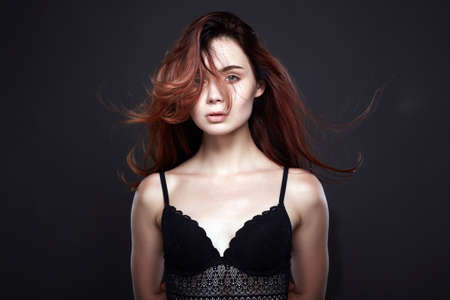 Flying hair Pretty Girl in black underwear. Healthy Red Hair Beautiful Young Woman