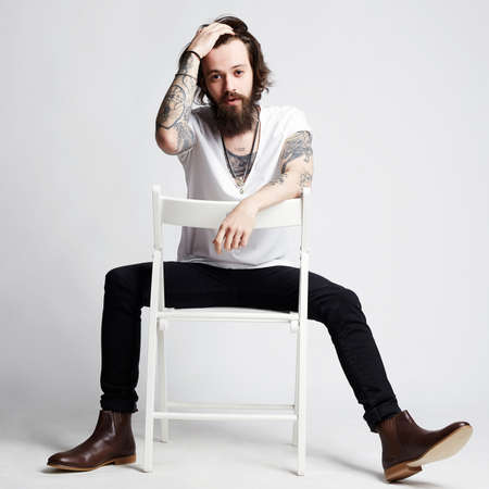 Tattooed handsome Man sitting on a chair. hipster boy with tattoo Banco de Imagens