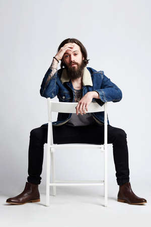 Tattooed handsome Man in denim coat, sitting on the chair. hipster boy with tattoo Banco de Imagens