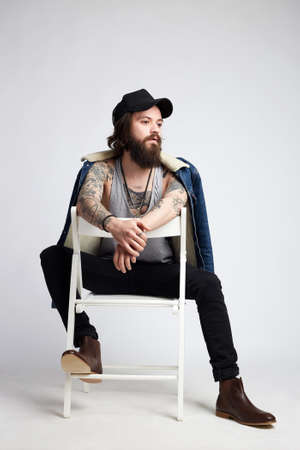 Tattooed handsome Man in hat and denim coat, sitting on the chair. hipster boy with tattoo