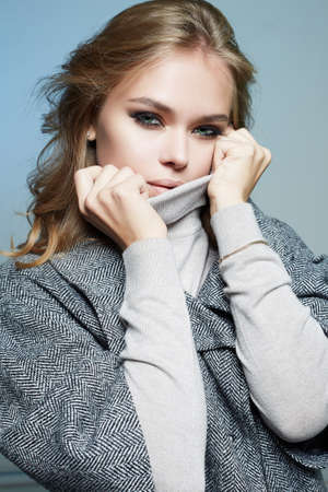 beautiful Woman with curly blond hair. Beauty Fashion Girl in topcoat. winter Shopping Banco de Imagens
