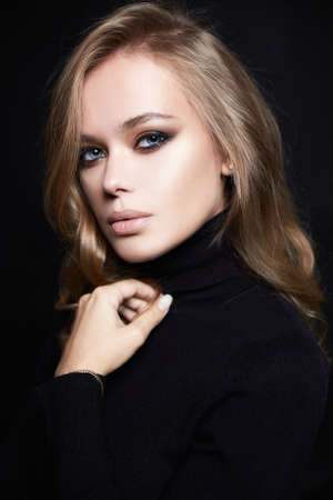 portrait of Beautiful young woman in black. sensual girl with make-up and curly blond Hair