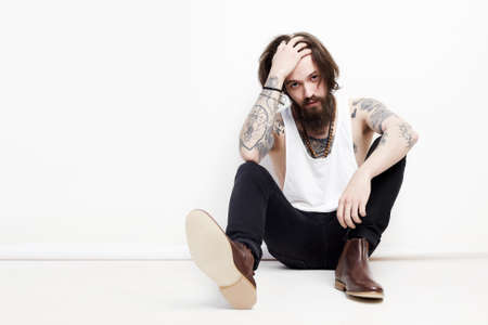 fashion portrait of handsome man in shoes. bearded boy with tattoo sitting in studio Banque d'images