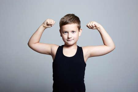 strong Child. Funny Little Boy.Sport Handsome Boy.bodybuilder showing his hand biceps muscles Banco de Imagens