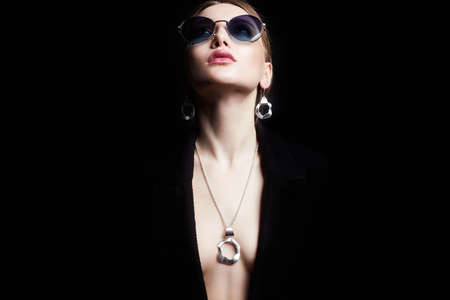 fashion portrait of Beautiful sexy woman in jewelry and sunglasses. sexual girl over black background Banco de Imagens