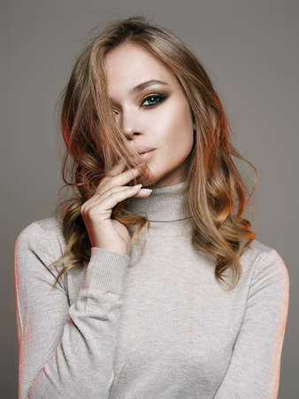 Beautiful young woman. sensual beautiful girl with make-up and curly blond Hair Banco de Imagens
