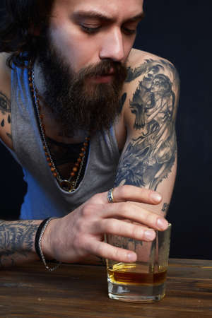 man with beard and tattoo. man drink whiskey. bearded hipster boy in Bar Banco de Imagens