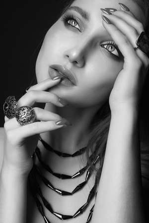 pretty young woman with jewelry. beautiful girl with make-up. black and white portrait