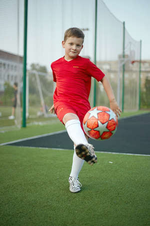 Little Boy Playing Soccer. Sport kid. Child with Ball on the sport field. Football player