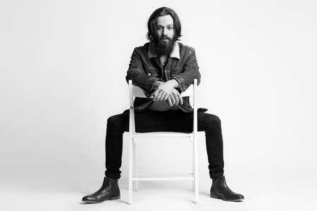Schwarz-Weiß-Porträt eines gutaussehenden Mannes in Schuhen und Jeansmantel, der auf dem Stuhl sitzt