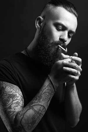 handsome Brutal bearded smoking man. Hipster tattoed boy with cigarette Banque d'images
