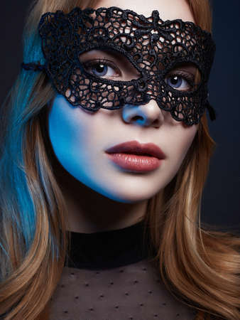 Beautiful young Woman in Mask. Color Lights. Sexy Girl in mask. Beauty & Fashion Stockfoto