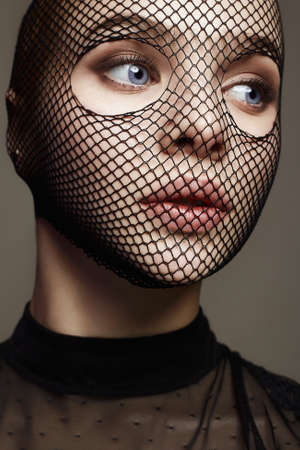 Beautiful Woman in Net on her Face. Sexy Girl in mask. Beauty & Fashion