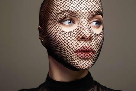 Beautiful Woman in Net on her Face. Pretty Girl in mask. Beauty & Fashion Stockfoto