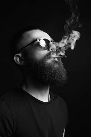 handsome bearded smoking man in glasses. Hipster boy with cigarette