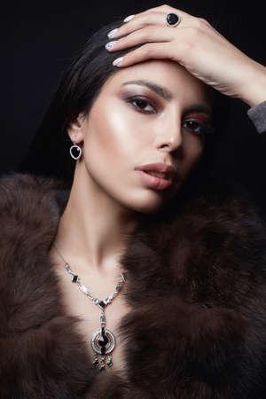 Schönes arabisches Mädchen in Schmuck und Pelz. Schönheits-Frau im Luxuspelz. Make-up und Accessoires Standard-Bild