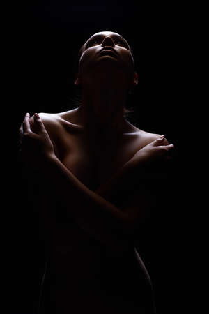 Nude Woman silhouette under light in the dark. Beautiful Sexy Naked Body Girl