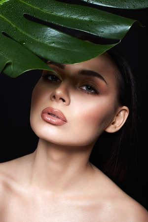 beautiful girl under palm umbrella. Beautiful young woman with Make-up. Beauty Portrait. Natural cosmetics Stock Photo