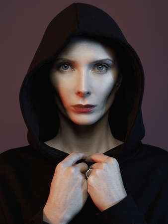 beautiful woman in hood and red lips. black Widow in hoodie Stockfoto