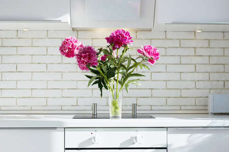 Fresh bouquet of peonies on a kitchen table. Beautiful Flowers in contemporary interior 免版税图像