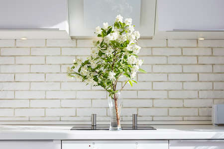 Jasmine on a kitchen table. Beautiful Flowers in contemporary interior. Fresh bouquet of jasmin