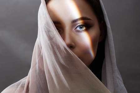 beautiful young woman covered her face. beauty girl in sunlight. fashion oriental style woman. ethnic people