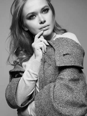 black and white portrait of Beautiful woman. Fashionable girl in coat