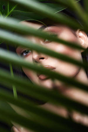 beautiful girl behind the palm. Beautiful young woman with Make-up. Beauty Portrait. Natural cosmetics