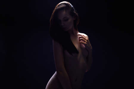 Nude Woman. Female silhouette under light in the dark. Beautiful Naked Body Girl. Black and white 免版税图像