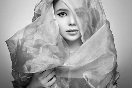beautiful young woman in veil. beauty girl in hood. black and white portrait