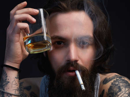 man with glass of alcohol and cigarette. smoking hipster boy with beard and tattoo.