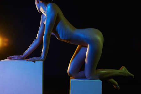 Nude Woman in Colorful bright lights. Beautiful Naked body of Girl on Cube in studio