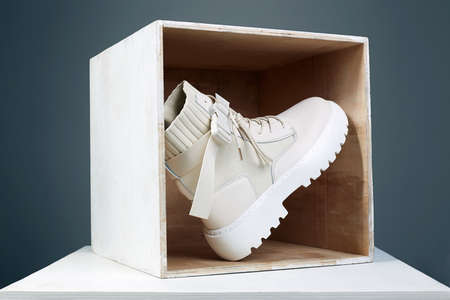 white boots in wooden box. fashion shoes still life. stylish photo in the studio